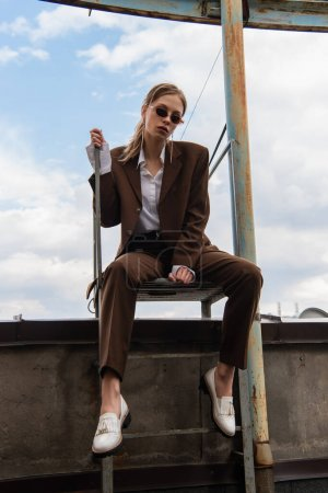 Photo for Full length of young model in stylish sunglasses and trendy suit sitting on metallic stairs on rooftop - Royalty Free Image