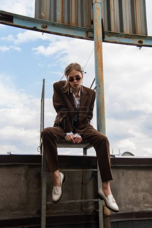 full length of young woman in sunglasses and trendy suit sitting on metallic rusty stairs on rooftop