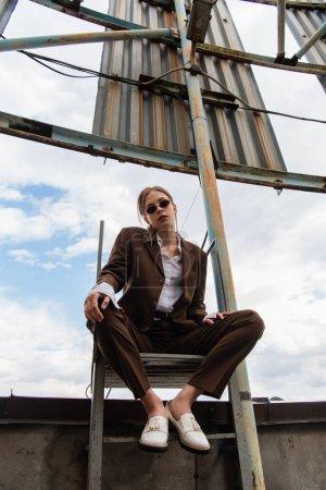 vue à angle bas de la jeune femme en lunettes de soleil et costume brun assis sur des escaliers métalliques sur le toit
