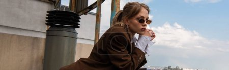 Photo for Thoughtful model in stylish sunglasses posing on rooftop with cityscape on blurred background, banner - Royalty Free Image