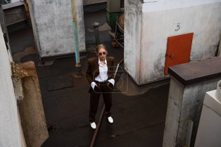 Photo for High angle view of stylish blonde model posing with hands in pockets on rooftop - Royalty Free Image