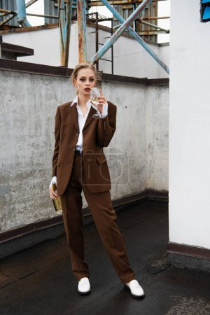 Photo pour Pleine longueur de jeune femme en costume élégant tenant bouteille et boire du vin sur le toit - image libre de droit