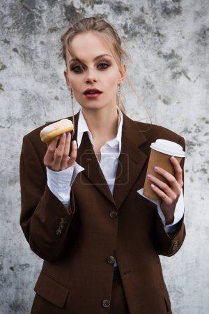 Photo pour Jeune femme en tenue élégante tenant tasse en papier et beignet contre mur en béton - image libre de droit