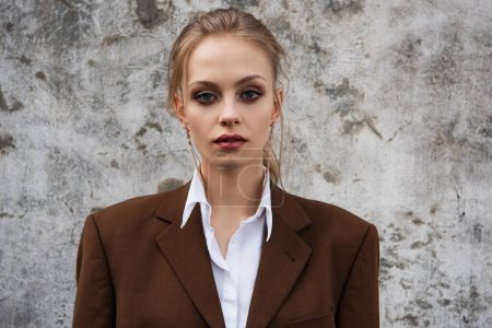 Photo for Young woman in stylish brown blazer posing near concrete wall - Royalty Free Image