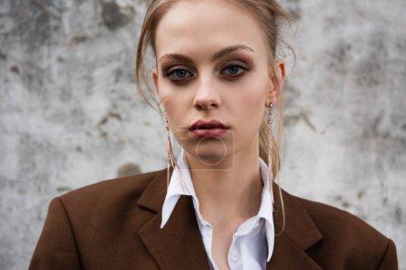 Photo pour Jeune femme en blazer brun à la mode posant près du mur de béton - image libre de droit