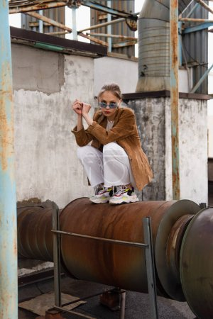 full length of young woman in stylish outfit with suede blazer and sunglasses posing on rusty construction