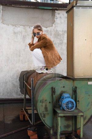 longitud completa de la mujer bonita en traje elegante con chaqueta de gamuza y gafas de sol azules posando en la construcción oxidada