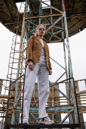 Photo for Low angle view of pretty young model in blue sunglasses, white pants and suede jacket posing near construction on rooftop - Royalty Free Image