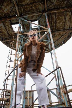 Photo pour Vue à angle bas du modèle en lunettes de soleil bleues, pantalon blanc et veste en daim posant près de la construction sur le toit - image libre de droit
