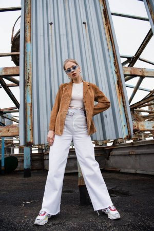 Photo for Full length of pretty young model in blue sunglasses posing with hand on hip near rusty construction on rooftop - Royalty Free Image