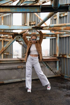Photo for Full length of pretty young model in blue sunglasses posing near weathered construction on rooftop - Royalty Free Image