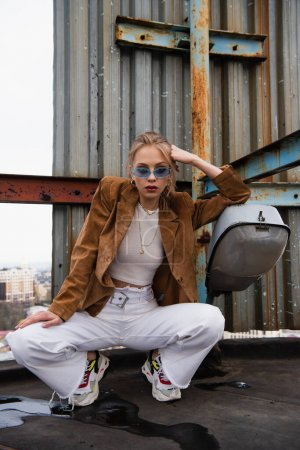 trendy model in blue sunglasses and stylish outfit sitting while posing on rooftop