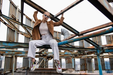Photo for Blonde woman in blue sunglasses and suede jacket sitting on rusty construction of rooftop - Royalty Free Image