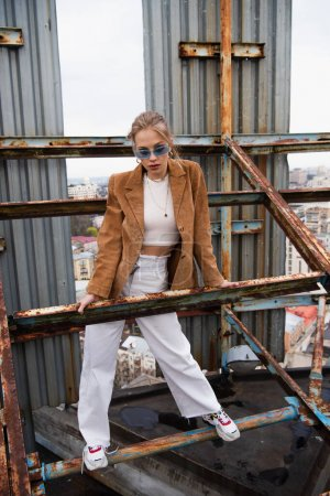 Photo for Full length of young woman in blue sunglasses and trendy outfit standing on weathered construction of rooftop - Royalty Free Image
