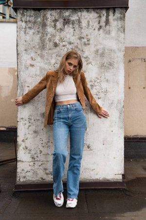 Photo pour Pleine longueur de femme en jeans denim, veston en daim et baskets élégantes posant près du mur en béton sur le toit - image libre de droit