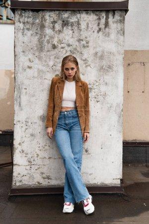 Photo pour Longueur totale du modèle en jeans, blazer en daim et baskets élégantes posant avec jambes croisées près du mur de béton sur le toit - image libre de droit