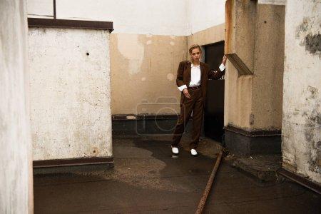 Photo pour Pleine longueur de modèle blond élégant en costume tendance posant sur le toit - image libre de droit