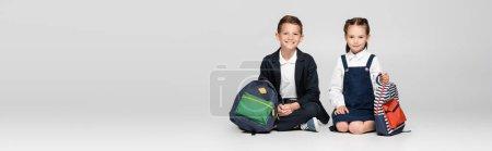 Photo pour Heureux écoliers en uniforme prestigieux assis avec des sacs à dos sur gris, bannière - image libre de droit