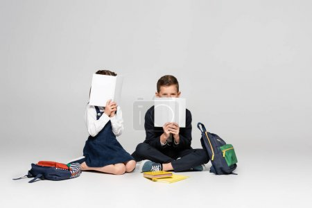 schoolkids in uniform sitting and covering faces with books near backpacks on grey