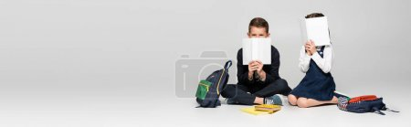 Photo for Schoolkids in uniform sitting and covering faces with books near backpacks on grey, banner - Royalty Free Image
