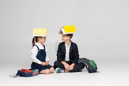 Photo pour Heureux écoliers en uniforme avec des livres sur les têtes assis et se regardant sur le gris - image libre de droit