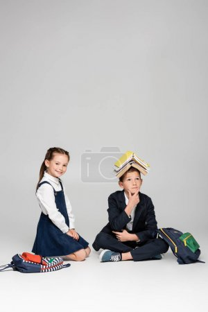 pensive schoolboy with books on head sitting near cheerful girl on grey