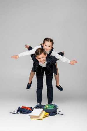cheerful schoolboy piggybacking girl with outstretched hands on grey