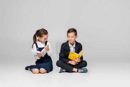 Photo pour Écoliers assis avec des livres et souriant sur gris - image libre de droit