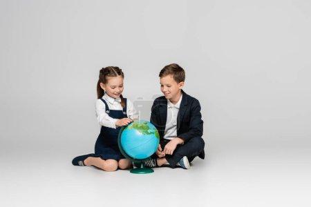 glückliches Schulmädchen und Schuljunge, die Globus betrachten, während sie auf grau sitzen
