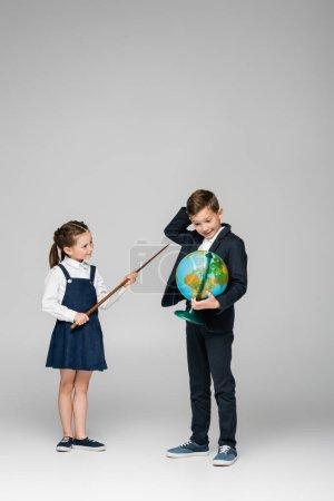 Photo pour Écolière souriante tenant bâton de pointage près garçon confus avec globe sur gris - image libre de droit