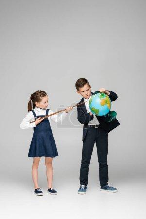 Photo pour Écolière tenant bâton de pointage près garçon avec globe sur gris - image libre de droit
