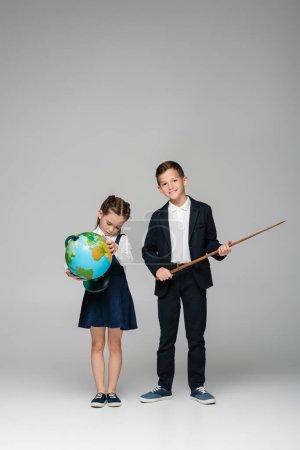Photo pour Joyeux écolier tenant bâton de pointage près fille triste en robe avec globe sur gris - image libre de droit
