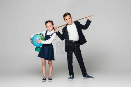 Photo pour Heureux écolier tenant bâton de pointage près fille souriante en robe avec globe sur gris - image libre de droit