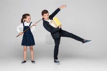 Photo pour Écolière tenant bâton pointant près de joyeux écolier en uniforme tenant pile de livres sur gris - image libre de droit