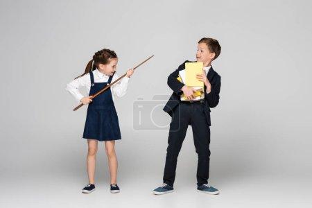 Photo pour Écolière souriante tenant un bâton pointant et menaçant écolier en uniforme avec pile de livres sur gris - image libre de droit