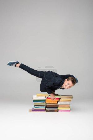 Photo pour Heureux écolier faire handstand sur pile de livres sur gris - image libre de droit