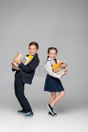 Photo pour Heureux écoliers tenant pile de livres sur gris - image libre de droit
