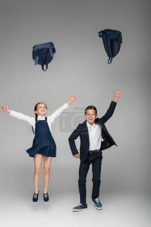 Photo pour Heureux écoliers jetant des sacs à dos dans l'air sur gris - image libre de droit