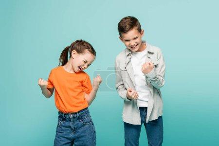 Photo pour Enfants excités avec les yeux fermés se réjouissant isolé sur bleu - image libre de droit