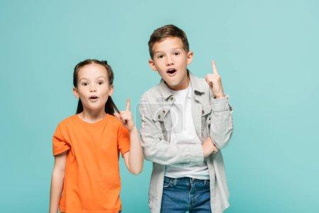 Photo pour Excités enfants pointant vers le haut avec les doigts tout en ayant idée isolé sur bleu - image libre de droit