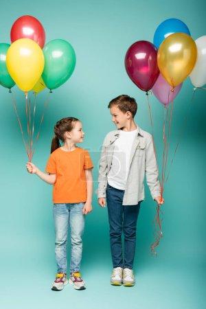 Photo pour Enfants heureux qui se regardent tout en tenant des ballons colorés sur bleu - image libre de droit
