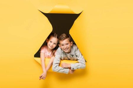 Photo pour Enfants heureux regardant caméra à travers le trou sur fond jaune - image libre de droit