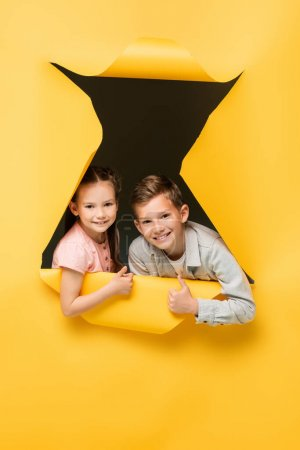 Photo for Happy kids showing thumbs up and looking at camera through hole on yellow background - Royalty Free Image