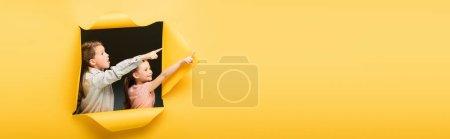Photo pour Enfants pointant loin avec les doigts à travers le trou sur fond jaune, bannière - image libre de droit