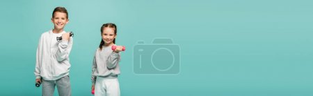 happy kids in sportswear working out with dumbbells isolated on blue, banner