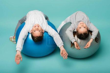 Photo pour Enfants heureux en vêtements de sport travaillant sur des balles de fitness sur bleu - image libre de droit