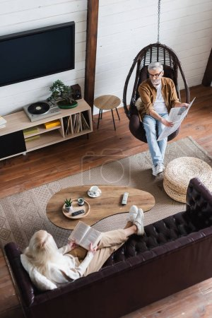 Overhead view of man pointing at newspaper near senior wife with book in living room