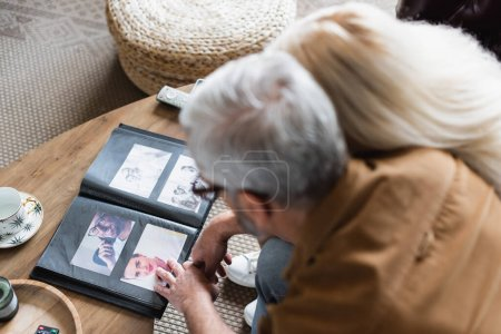 Photo for Overhead view of blurred elderly couple sitting near photos in album on table - Royalty Free Image