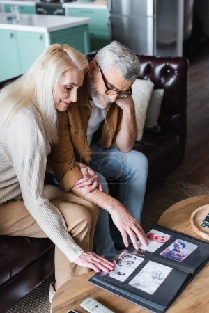 Ältere Familie betrachtet Fotos im Album auf Couchtisch