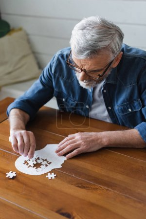 Photo for Senior man with dementia holding puzzle on table - Royalty Free Image